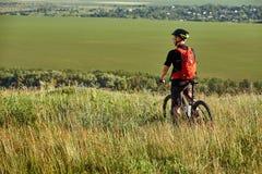 La vista posterior del deportista con su bici de montaña se coloca en el prado y la mirada lejos en el campo Imagen de archivo libre de regalías