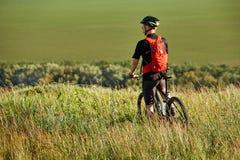 La vista posterior del deportista con su bici de montaña se coloca en el prado y la mirada lejos en el campo Foto de archivo