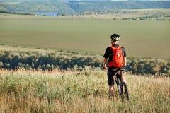 La vista posterior del deportista con su bici de montaña se coloca en el prado y la mirada lejos en el campo Imagen de archivo