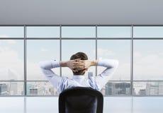 La vista posterior del hombre de negocios relajante está en una oficina panorámica moderna Imagen de archivo