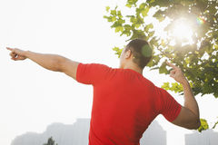 La vista posterior del hombre muscular joven que estira por un árbol, arma aumentado y los fingeres que señalan hacia el cielo en  Imagen de archivo