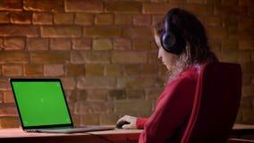 La vista posterior del primer del blogger joven en sudadera con capucha roja y los auriculares que trabajan con el ordenador port almacen de metraje de vídeo