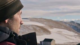 La vista posterior del primer de un hombre caucásico en una chaqueta caliente y del sombrero en el invierno en las montañas mira  almacen de metraje de vídeo