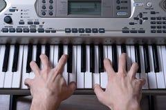 La vista posterior frontal del ` s de las mujeres da jugar las llaves del piano electrónico fotos de archivo