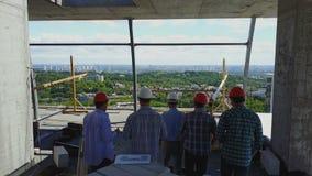 La vista posterior trasera de la antena del grupo de los constructores en emplazamiento de la obra, ingenieros en el edificio se  metrajes