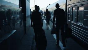 La vista posteriore di un uomo e di un trasporto di camminata della donna insacca sul binario del treno Lotti della gente sui pre video d archivio