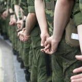 La vista posteriore I soldati in uniformi del cammuffamento stanno sulla mani Immagini Stock Libere da Diritti
