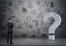 La vista posteriore punto interrogativo concreto commovente 3D dell'uomo d'affari di grande sul backgound con l'affare scarabocch Fotografia Stock Libera da Diritti