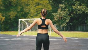 La vista posteriore sul giovane atleta Woman in attrezzatura di sport si è impegnata nella forma fisica sul campo sportivo nel pa video d archivio