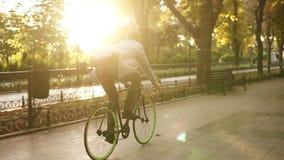La vista rara de la bici del montar a caballo del hombre joven en el parque y escucha la música en auriculares negros Hombre que  metrajes