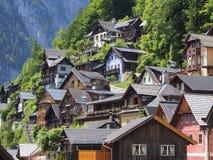 La vista scenica di vecchie case di legno tradizionali aumenta la collina nel paesino di montagna famoso di Hallstatt immagine stock