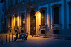 La vista serena de una pequeña moto parqueó en un callejón en Milán Foto de archivo