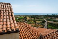 La vista sopra i tetti piastrellati arancio verso i campi e la posada tirano, la Sardegna fotografia stock