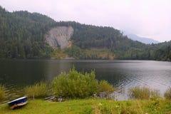La vista sopra sul lago delle montagne con la barca bianca blu sulla priorità alta Fotografia Stock Libera da Diritti