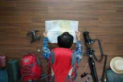 La vista sopraelevata della vacanza di piano dell'uomo del viaggiatore e di pianificazione dello zaino viaggia Immagine Stock