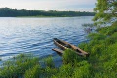 La vista sul fiume con la barca di legno si è sovrapposta vicino alla via di accesso principale sulla riva immagini stock