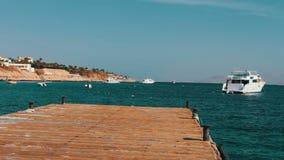 La vista sul mare con il pilastro di legno contro lo sfondo dell'yacht bianco galleggia stock footage