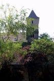 La vista sulla casa medievale con gli alberi sulla priorità alta Immagine Stock