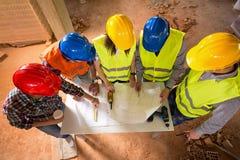 La vista superior de cascos coloridos de arquitectos en la construcción se sienta imagen de archivo