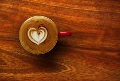 La vista superior de la espuma blanca de la crema de la leche del corazón del capuchino del café encendido corteja Fotos de archivo libres de regalías