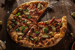 La vista superior de la pizza cocida fresca sin rebanada sirvió en etiqueta de madera Foto de archivo