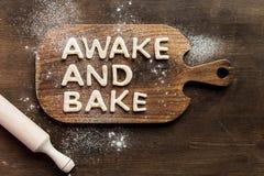 La vista superior de las letras comestibles despierta y cuece hecho de la pasta en tabla de cortar de madera Imagen de archivo