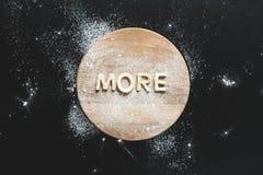 La vista superior de las letras comestibles hizo más de las galletas en tabla de cortar de madera Fotos de archivo