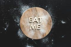 La vista superior de las letras comestibles me come de la pasta en tabla de cortar de madera Imagen de archivo libre de regalías