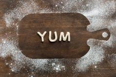 La vista superior de las letras comestibles yum hizo de las galletas en tabla de cortar de madera Imagen de archivo