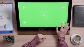 La vista superior de las manos de un hombre toca la esquina inferior derecha de una pantalla verde en monitor del tacto almacen de metraje de vídeo