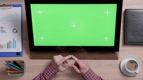 La vista superior de las manos de un hombre toca la esquina izquierda inferior de una pantalla verde en monitor del tacto almacen de video