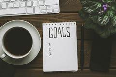 La vista superior de la libreta con metas enumera, taza de café en la tabla de madera, concepto de las metas Fotografía de archivo libre de regalías