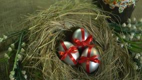 La vista superior de los huevos de plata en una cinta roja en la jerarquía y Pascua se apelmazan, tiroteo del resbalador metrajes