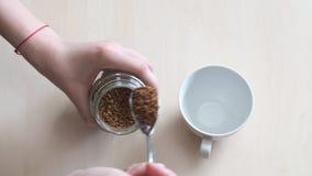 La vista superior de la mano pone la cucharada dos de café instantáneo en taza metrajes