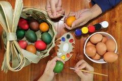 La vista superior de manos de miembros de la familia está pintando los huevos con una brocha y una paleta en la tabla de madera p imágenes de archivo libres de regalías