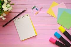 La vista superior de la página en blanco del cuaderno en pastel coloreó el escritorio de oficina del fondo con diversos objetos E Foto de archivo