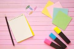 La vista superior de la página en blanco del cuaderno en pastel coloreó el escritorio de oficina del fondo con diversos objetos E Imagen de archivo libre de regalías