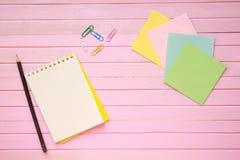 La vista superior de la página en blanco del cuaderno en pastel coloreó el escritorio de oficina del fondo con diversos objetos E Imagen de archivo