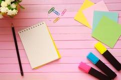 La vista superior de la página en blanco del cuaderno en pastel coloreó el escritorio de oficina del fondo con diversos objetos E Imagenes de archivo