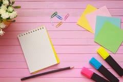La vista superior de la página en blanco del cuaderno en pastel coloreó el escritorio de oficina del fondo con diversos objetos E Fotos de archivo libres de regalías