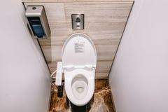 La vista superior de la taza del inodoro moderna, y el papel higiénico en el cuarto blanco son lavabo público foto de archivo libre de regalías