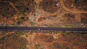 La vista superior de un coche monta a lo largo de un camino del desierto en Tenerife, islas Canarias, España almacen de video