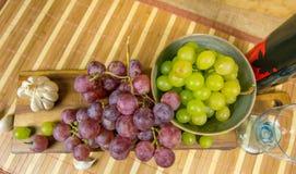 La vista superior de un moscatel rojo y amarillo coloreó la uva, la botella de vino, el ajo y un vidrio en un tablero de madera - Fotografía de archivo