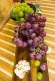 La vista superior de un moscatel rojo y amarillo coloreó la uva, la botella de vino, el ajo y un vidrio en un tablero de madera - Imagenes de archivo