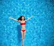 La vista superior del bikini atractivo bronceó la natación modelo de la muchacha en el océano azul foto de archivo