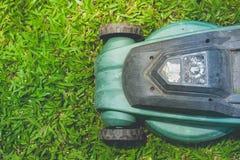 La vista superior del cortacésped está trabajando en hierba verde en el jardín al aire libre con el fondo de la luz del sol imagen de archivo libre de regalías
