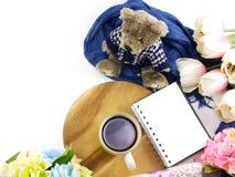 La vista superior del cuaderno de la taza de café de la mañana con las flores y la bufanda en copia espacian el fondo blanco Fotografía de archivo libre de regalías
