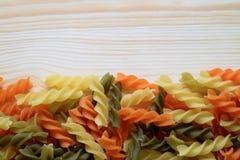 La vista superior del espiral tricolor crudo formó las pastas o Fusilli en la tabla de madera fotografía de archivo libre de regalías