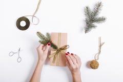 La vista superior del las manos femeninas embala y adorna la caja con los regalos Fotos de archivo libres de regalías