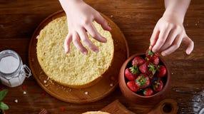 La vista superior del ` s de la muchacha da el adornamiento de una torta con las fresas, primer, foco selctive, vertical Foto de archivo libre de regalías